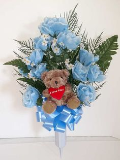 "Teddy bear memorial flower vase with blue roses.  The heart around the bear's neck reads, ""I Love You""."