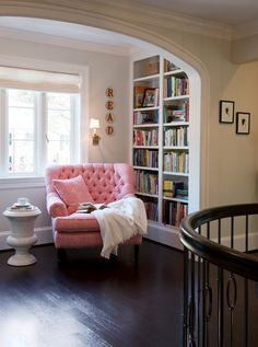 Cozy reading nook. Wood floors, built-in bookcase, arched doorway, large window.