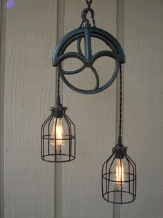 Two bare bulbs, caged, on a pulley system.