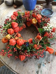 Herfstkrans van hop, kornoelje, viburnum, rozenbottel en lampionplant