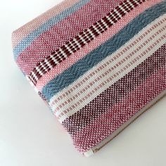 One of a kind zipper pouch. The textiles for this pouch have been hand woven on our eight shaft loom, using our hand dyed wool yarn. The pouch is lined with natural, unbleached cotton fabric and features a strong metal zip with a leather tassel. Both sides feature the same colour palette but the stripe patterns are different. Measurements: approx 9in by 7 in