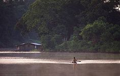 Casa flotante y hombre en canoa en Amazonia.  © Roger Leguen / WWF