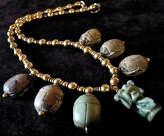 View 1: Old Egyptian Necklace with Scarabs - Seven amulets from Old Egypt, pierced with a hole for hanging, and dangling from a 19th century necklace consisting of a mix of small and average size 14-karat gold pearls. Six green and brown beetles in soapstone of brownish and greenish color, the flat backside decorated with hieroglyphs, framing a central amulet in green turquoise porcelain.