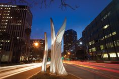 """The elegant steel curves of public artist Barbara Grygutis's """"Seagrass"""" stretch towards the ocean-blue sky, as though rippling and swaying in a larger-than-life seabed. The three-piece sculptural composition with integral lighting is located downtown in the median of Ocean Boulevard, at Chestnut Avenue, directly across from the Long Beach County Courthouse, and is an artistic reminder of the importance and beauty of ocean life to metropolitan Long Beach."""