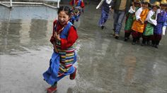 An exiled Tibertan girl wearing a traditional costume runs through the rain to her school hall for a display of dancing in the Indian hill town of Dharamsala.  From BBC 8.15.2011 (http://www.bbc.co.uk/news/world-14528416)