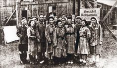 "Women's concentration camp victims smile before ""Warning! High voltage"" sign at concentration camp"