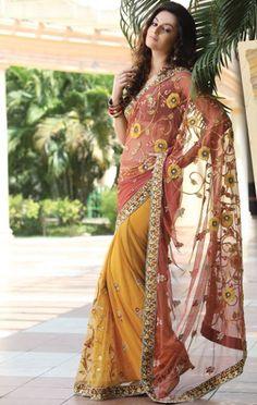 This light brick and mustard net saree with blouse.      Saree is arrayed with resham, sequins, salma, stone and patch patti work in form of floral motif.      Broad embroidered patch patti work is making this beautiful saree look more classy.      Matching blouse piece is available with the saree. Approx $106.79