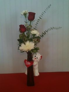 SOLD OUT!   BEAR HUG   Item# VD01  As Shown $35.00     This beautiful bud vase includes red roses, white carnations, white fuji's, wax flowers, and eucalyptus beautifully arranged in a red vase with a complimentary white bear wrapped around with a heart.       Ask us about upgrading your arrangement:   Deluxe $45.00  Premium $55.00    Limited Availability! $35!!!!