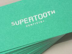 Smile-shaped logo on business cards for Supertooth Dentistry.
