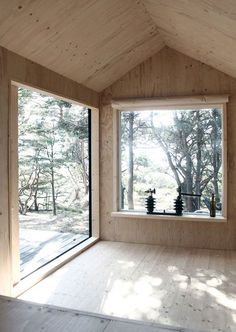 This tiny wooden cabin in Sweden contains a sauna and a bedroom with large picture windows that frame views of the surrounding forest