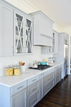 Showhouse kitchen: soft gray cabinets with x-fronted glass & leathered marble