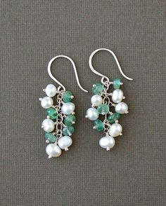 These emerald pearl earrings feature genuine emerald rondelles and freshwater pearls that cascade from shepards hook ear wires. The ear wires are