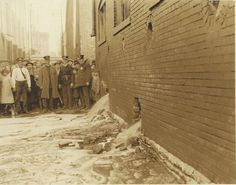 St. Louis police officers from the Carr Street Station supervising the draining of a mash vat in an illicit Franklin Avenue distillery during Prohibition.
