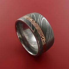 This 10mm wide DAMASCUS ring has a 2mm Off Center groove, inlaid with a deep 14K ROSE GOLD and SHAKUDO a gold/copper alloy) that is twisted together to obtain the design in a ACID FINISH. Each ring is
