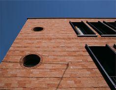 素焼きレンガCottoを使用した外壁。デプスウィンドウに収まるフォールディングタイプの鎧戸。