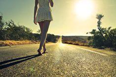 Mujer caminando descalza por la carretera