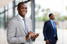 young african businessman reading email on smart phone stock photo
