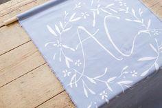 Banderole de bienvenue, en tissu gris bleuté, calligraphié à la main. Organisation et Décoration: Atelier Blanc ATLB  Crédit Photo: Romain Deligny