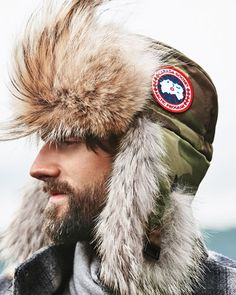 Canada Goose aviator hat with natural coyote (Canada) fur visor and ear flaps. Water-resistant exterior fabric for durability. Canada Goose logo patch on side. Adjustable buckle chin strap. Polyester/