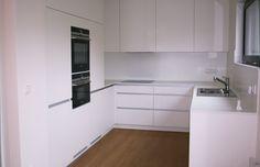 Bílá kuchyně v dřevostavbě.
