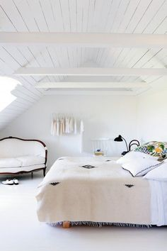 White bedroom with shiplap walls, exposed beams in the ceiling and a French love seat in the corner.