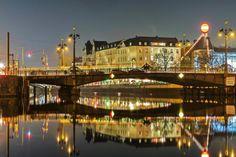 Die Weidendammer Brücke und die dahinter liegenden Gebäude am Schiffbauerdamm spiegeln sich bei einer Langzeitbelichtung in der Spree. Die Brücke gehört zu den historisch bedeutendsten Spreequerungen in der Hauptstadt. Ihre Ursprünge als hölzerne Zugbrücke gehen bis ins 17. Jahrhundert zurück.