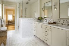 Modern traditional white marble bathroom with tan mosaic inlay on backsplash and floor; double sinks, grey off white custom vanity; frameless shower glass with no corner hardware