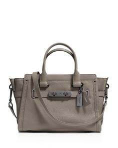 This charmingly compact version of the Coach Swagger carryall is crafted in pebble leather with a refined grain. The long strap clips on with ease for a hands-free carry; statement belting and double-