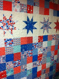 Star spangled star quilt using charm squares. Quilted with stars, hearts, flowers and lots of loops.