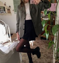 Necklace over a thin high neck shirt, skirt, tights, and boots