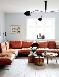 lædersofa fra i4mariani, bordene er et miks af Muuto-design og træstammer fra haven. På sofabordet står skåle fra Georg Jensen og vaser fra Kähler. Lampen er af den franske designer Serge Mouille