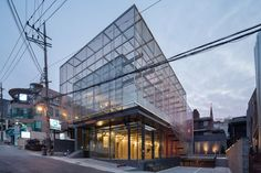 A cage-like structure made from strips of mirrored metal and red plastic encases this Seoul office building by South Korean studio Wise Architecture
