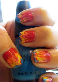 """Fire Nails: """"needle-dragging"""" or """"dry marbling"""" technique - 1. Apply a base coat of red..  2. While still wet, add small drops of orange, yellow, and blue on top..  3. Drag a needle through all the wet polishes to make the streaking effect"""