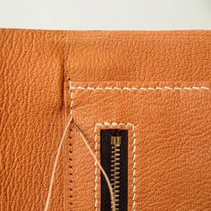 Leatherworking layers in focus - Many stages and processes go into bag making. This snap shot shows lining glued carefully onto the main body and a hand sewn hanging zip pocket then being stitched to the body piece. This fine orange goat leather makes a sumptuous lining #leatherwork #leathercraft #leather #vegtan #artisan #atelier #craftsmanship #britishmade #madeinlondon #madeinhackney #handcrafted #handstitched #makersgonnamake #carv  layers - Many stages and processes go into bag making…