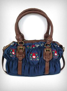 Gnome & Mushrooms Satchel Bag  This adorable duffle style satchel bag is made of navy blue canvas and features retro Gnomes & Mushrooms embroidered on the front and across the top, chocolate brown leather like trim and braided handles, and antiqued brass hardware. The interior has one large main compartment with a small zippered pocket, a cell phone pocket, and an accessory pocket for small items.