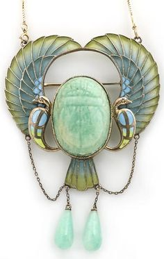 A Egyptian revival plique-à-jour enamel and amazonite scarab pendant/brooch, circa 1920, with modern fourteen karat gold chain. Carved amazonite scarab flanked to either side with stylised peacocks, each with an outstretched wing and suspending an amazonite drop; mounted in silver.