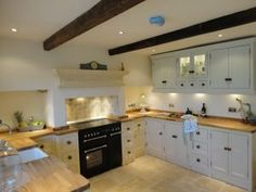 One of our favourite kitchen pictures! The creamy white 'tallow' units give this freestanding kitchen such a light airy feel,with oak worktops and matching knobs,broken up with the black range cooker.