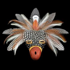 D. R. Nance is a Native American (Lumbee) artist who has earned his fame making masks. He paints dried gourds and attaches a colorful array of natural feathers to match.