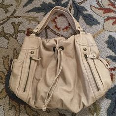 Tan shoulder purse with zippers and drawstring One of my favorites! A pen got loose and made and stained the liner. My loss is your gain! Lots of life left with this gorgeous purse. Bueno Bags Shoulder Bags