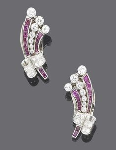 A pair of art deco ruby and diamond earclips, circa 1935  Each in the form of a brilliant-cut diamond and calibré-cut ruby openwork scroll with brilliant-cut diamond three-stone finial gathered by a single-cut diamond ribbon, diamonds approx. 1.70ct. total, length 3.2cm., fitted case by Garrard & Co.