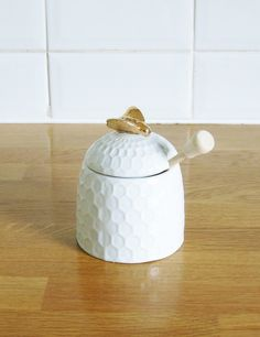 It's not just bees who love honey! This ceramic honey pot has a textured honeycomb design and gold bee detail on lid. Comes with a natural wood honey dipper