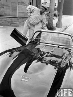 Steve Mcqueen with his rare Jaguar XK SS. A road legal version of the Le Mans D Type. A fire at the factory destroyed all but 16 cars. The Mcqueen car was originally white with red leather interior. He had it painted British racing green, with black leather interior. It was knicknamed 'the green rat' and was probably his favorite car.