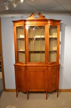 An Edwardian Period satinwood serpentine antique display cabinet by Maple & Co.