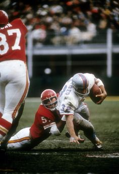 Jim Lynch of the Kansas City Chiefs tackles Hoyle Granger of the Houston Oilers during an AFL football game at Kansas City Municipal Stadium