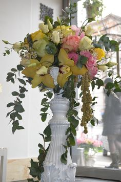 Table centerpiece made on ceramic candleholder,with yellow cimbidium orchid flowers,cinerea eucalyptus,eryngium questar,white and pink lisianthus,white wax flower,amaranthus and mixed roses,designed by Adrian Ionita