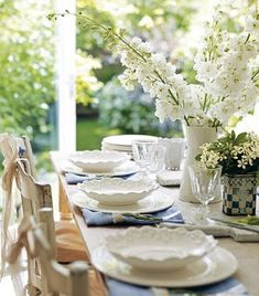 table set with white plates & flowers