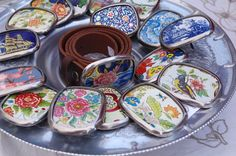 Belt buckles fashioned from vintage biscuit tins