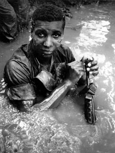 A U.S. 9th Infantry Division soldier of the 2nd Battalion, 60th Infantry, takes advantage of a stream in the Mekong Delta of South Vietnam to cool off while cleaning his weapon in June 1969 during the Vietnam War.