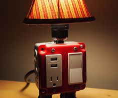 Charge your devices and give off some warm lighting in your home or office with this clever USB charger outlet lamp. Available in a several different colors, this unique forty watt lamp doubles as a electrical outlet and USB charger station.