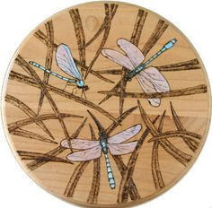 Pyrography / Woodburnt round plate or wall plaque. A nicely arranged design, not to much detail that would otherwise confuse the eye. The grass stalks could have used a bit more care perhaps but choosing to color only the dragon flys pushes them well into the background. This would be a good subject for a lazy susan too ;)